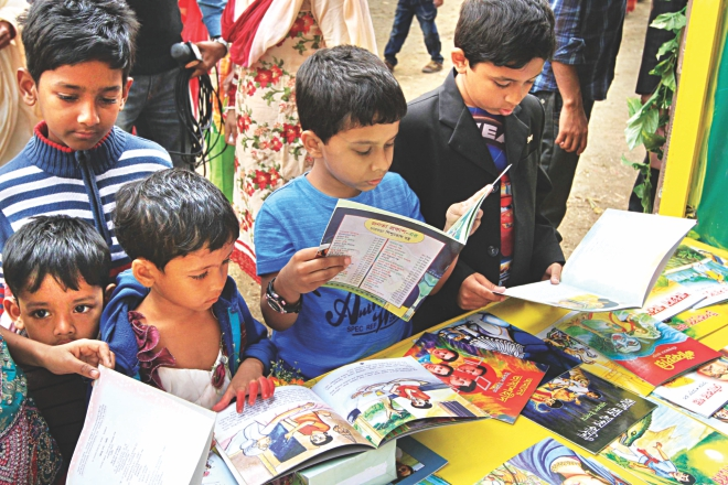 Children browse through books at a stall of Amar Ekushey Boi Mela on the Bangla Academy premises yesterday.  Photo: Palash Khan
