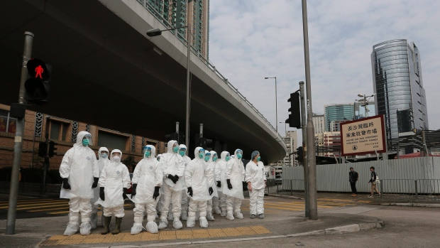 Caption: Health workers in full protective wait to get in a wholesale poultry market before culling the poultry in Hong Kong, January 28. Photo: AP