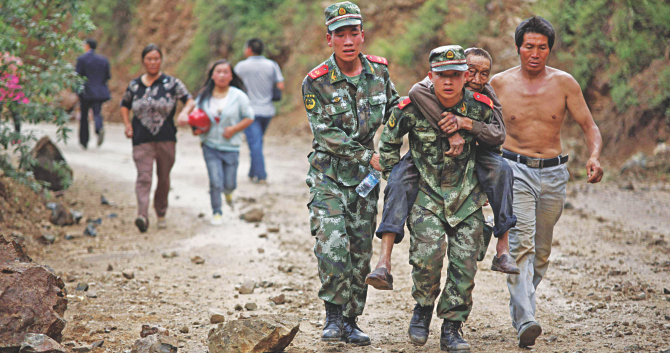 Rescuers carry an injured resident at Ludian county in Zhaotong. Photo: Reuters/AFP