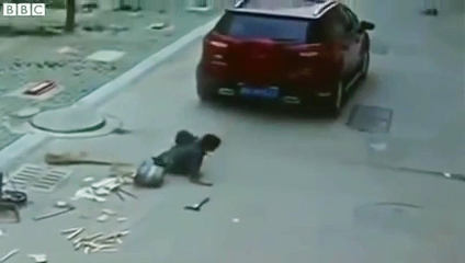 A still grab from the surveillance footage showing a Chinese boy pulling himself after being run over by an SUV.