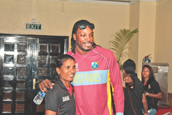 Bangladesh women's cricket team's captain Salma Khatun poses for a photograph with West Indies batsman Chris Gayle at the Ruposhi Bangla Hotel in Dhaka yesterday. PHOTO: SK ENAMUL HAQUE
