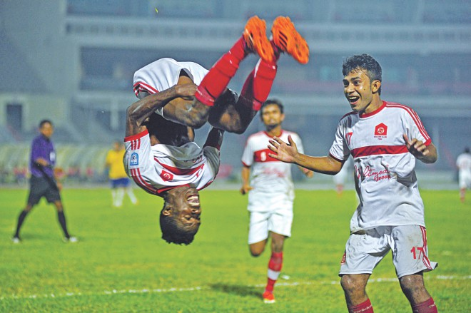 Nigerian striker Chuka Charles of Feni Soccer Club celebrates scoring one of his two goals with a somersault in their Bangladesh Premier League match against Team BJMC yesterday at the Bangabandhu National Stadium. Photo: Firoz Ahmed