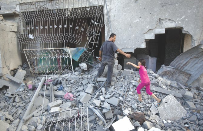 Palestinians walk through the rubble of a house. Photo: AFP