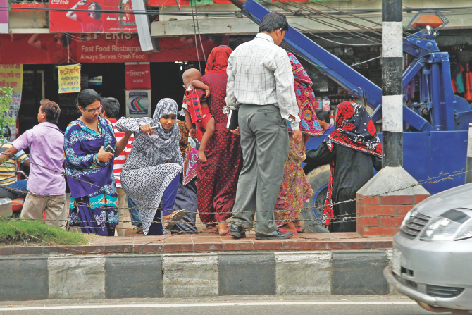 Pedestrians, however, risk their lives to cross the busy Kazi Nazrul Islam Avenue and sometimes they get tangled in the barbed-wire fence. Photo: Sk Enamul Haq