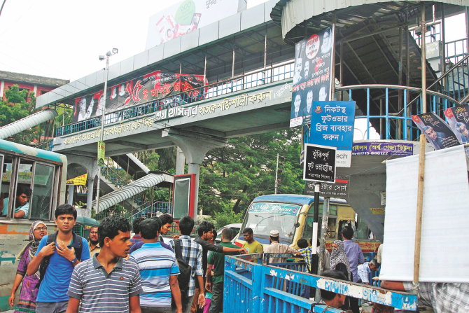 The footbridge is there at Farmgate but a sign, top, asks pedestrians to use other bridges close by. The bridge has been out of commission for over a month with no sign of authorities concerned trying to repair it.  Photo: Sk Enamul Haq