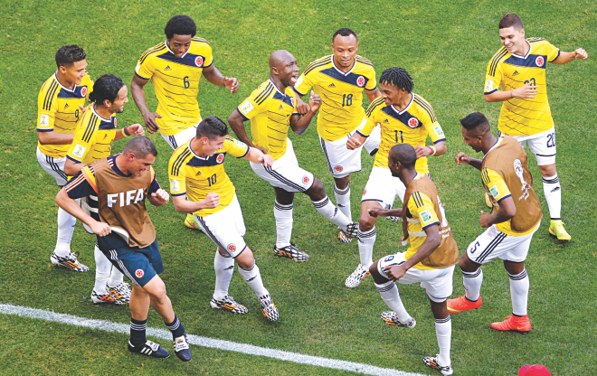 Colombia players dance to celebrate one of their two goals against Ivory Coast during a Group C match of the World Cup at the Mane Garrincha Stadium in Brasilia on Thursday. Colombia won the match 2-1.  PHOTO: AFP