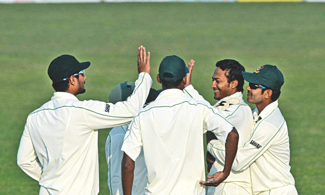 Shakib Al Hasan (2nd from R) is congratulated by teammates as his late double-strike brought smile to the Bangladesh camp at the end of the first day of the second Test against Sri Lanka at the Zahur Ahmed Chowdhury Stadium in Chittagong yesterday.  PHOTO: ANURUP KANTI DAS