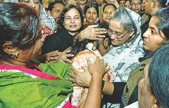 On the 10th anniversary of the August 21, 2004 grenade attack, Prime Minister Sheikh Hasina consoles a victim on Bangabandhu Avenue yesterday. Photo: PMO