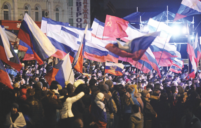 Pro-Russian Crimeans wave Russian flags as they gather to celebrate in Simferopol's Lenin Square on Sunday after exit polls showed that about 93 percent of voters in Ukraine's Crimea region supported union with Russia. Photo: AFP