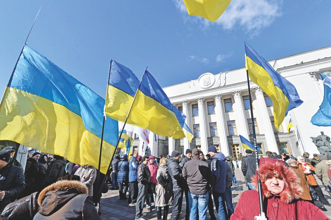People hold Ukrainian flags as they gather in front of the parliament in Kiev yesterday. Ukrainian troops will remain in Crimea, the country's defence minister said that day even as media reported the separatist peninsula planned to disband Ukrainian units there. Photo: AFP