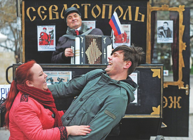 A man plays accordion as people dance during celebrations in Sevastopol yesterday. Crimea applied to join Russia after the flashpoint peninsula voted to leave Ukraine in a ballot that has fanned the worst East-West tensions since the Cold War. PHOTO: AFP