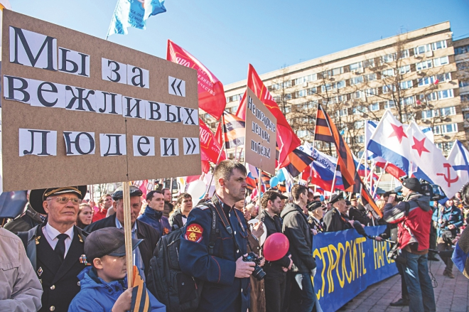 Pro-Kremlin activists hold Russian national, Russian and Soviet naval flags and orange-black flags made of the St George's Ribbons, a well-known Russian symbol of military valor, during a rally in support of ethnic Russians in Ukraine in central Moscow, yesterday. Photo: AFP