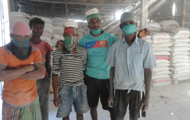 Workers use normal masks instead of professional ones at a limestone crushing factory in Burimari land port area in Patgram upazila of Lamonirhat.  PHOTO: STAR