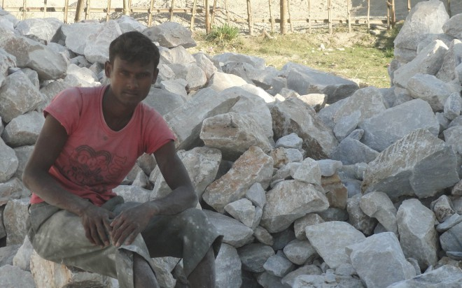 A worker without any mask takes rest on limestones. PHOTO: STAR