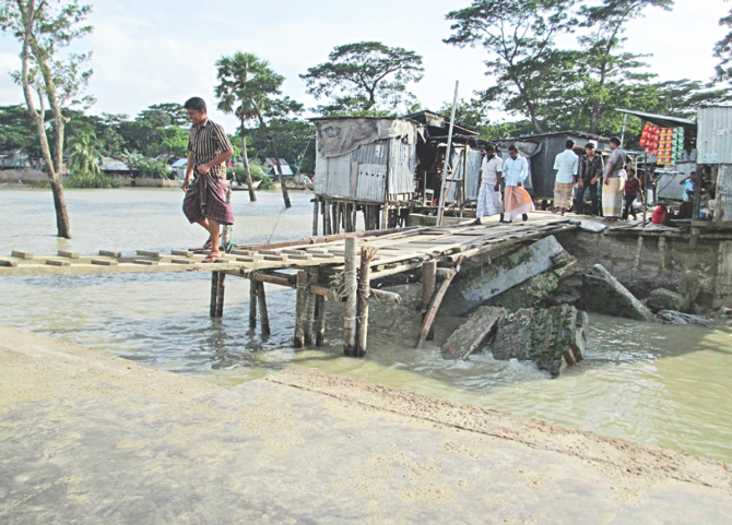 Passengers cross a risky wood and bamboo structure  to enter the pontoon. PHOTO: STAR