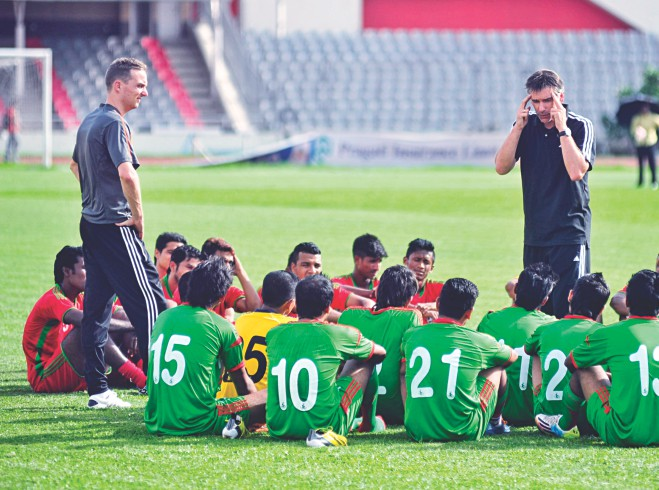 National football team's head coach Lodewijk de Kruif (R) briefs his charges as assistant coach Rene Koster (L) looks on after a practice match between the players at the Bangabandhu National Stadium yesterday. PHOTOS: STAR