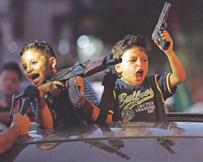 Children hold up guns from a car to celebrate the deal. Photo: AFP