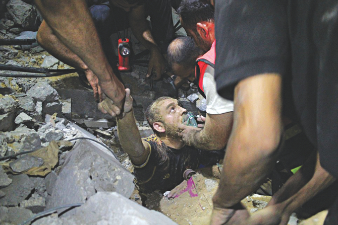 Rescue workers dig out a man from the ruins of an Israeli air strike late on Tuesday night. Israeli intensified air raids on Gaza yesterday as furious mourners buried the wife and child of Hamas's top military commander, baying for revenge as nine days of calm exploded into bloodshed.  Photo: Reuters