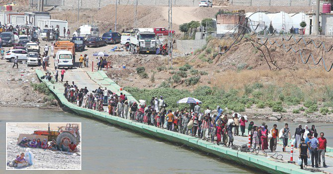 Displaced Iraqis from the Yazidi community cross the Iraqi-Syrian border along the Fishkhabur bridge over the Tigris River at the Fishkhabur crossing, in northern Iraq, yesterday. Inset: Others from the community shelter from the sun as they wait to cross the Iraqi-Syrian border. At least 20,000 civilians who had been besieged by jihadists on a mountain in northern Iraq have safely escaped to Syria and been escorted by Kurdish forces back into Iraq, officials said. Photo: AFP