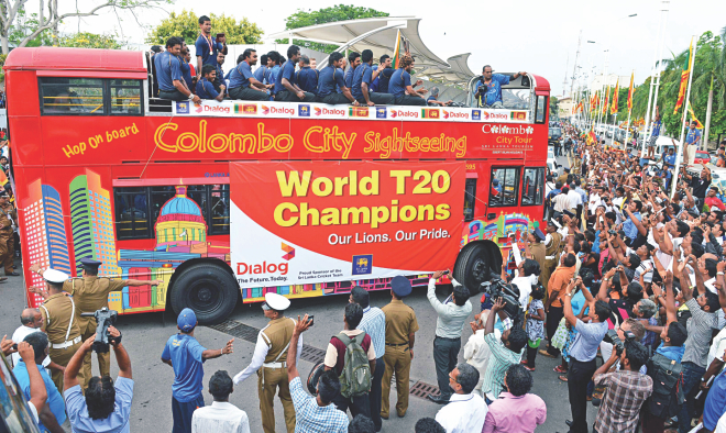 ICC World T20 champions Sri Lanka take a merry ride on an open-top bus as jubilant fans line the Colombo streets to greet their cricketing heroes yesterday. Photo: AFP