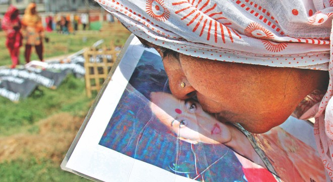 With all her love, Safura Khatun kisses the photo of her daughter Rashida, a Rana Plaza victim, near her grave at Jurain graveyard in the capital yesterday. She kept the photo with her for the last one year, looking for her child who was buried unidentified there before a DNA test confirmed her identity in February and paved the way for her family to know at least where she is laid to rest. Photo: Anisur Rahman