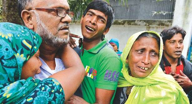 This courtesy file photo shows family members of Musa and Masud huddle together and cry. Musa and his son Masud, supporters of winning Jatiya Party candidate were killed on January 6 when supporters of defeated Awami League election candidate Mannan Khan attacked them at Hajarbigha of Dohar in Dhaka.