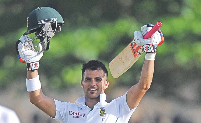 South Africa's JP Duminy raises his bat and helmet in celebration after scoring a century on the second day of the first Test against Sri Lanka at the Galle International Cricket Stadium yesterday. PHOTO: AFP