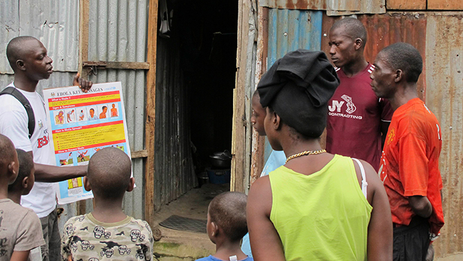 An outreach worker speaks with residents about the information on the symptoms of Ebola virus disease (EVD) and best practices to help prevent its spread, in Freetown, Sierra Leone in this August, 2014 handout photo provided by Unicef August 6. Photo: Reuters