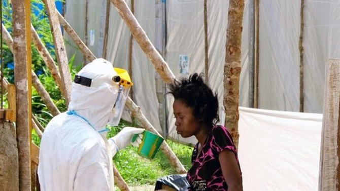 A health worker offers water to a woman with Ebola in Kenema, Sierra Leone, in July 2014. World Health Organization experts say it will take months to bring the outbreak under control. Photo: BBC