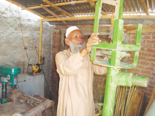 Abdus Sobhan checking the vertical pump at his workshop at Shailkupa upazila town. PHOTO: STAR