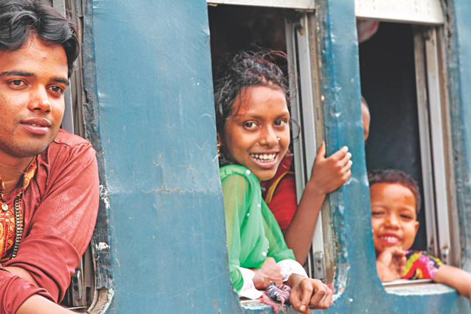 Happy faces at the windows of a train at Airport Railway Station in the capital yesterday. They were the lucky ones who had seats for their travel home on Eid holidays. Many others, not in frame, were standing in the aisle and sitting on the roof of the train. Photo: Sk Enamul Haq