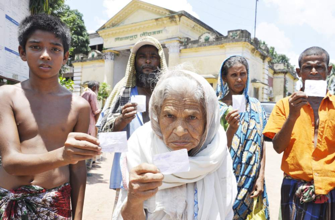 Five members of ultra poor families show their VGF cards issued by Dinapur municipality to provide them with only 3kg of rice instead of 10 kg under special Eid programme at the premises of the municipality office yesterday. Photo: Star