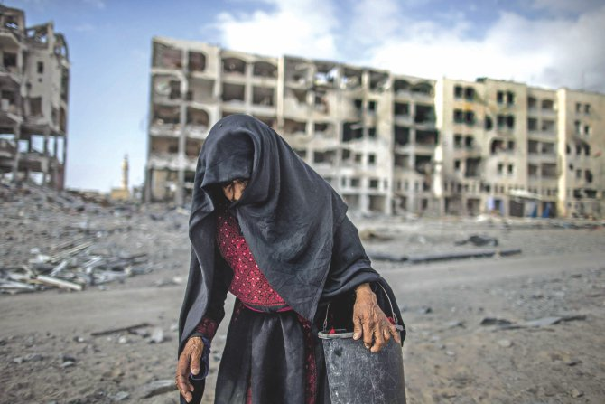 An elderly Palestinian woman carries a bucket as she walks past destroyed buildings in Beit Lahia in the northern Gaza Strip yesterday, with the Israeli-Hamas conflict entering its 27th day in the besieged territory.  Photo: AFP