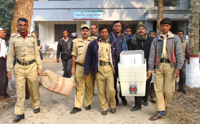 Polling officials with the help of law enforcers take election materials, including ballot papers and ballot boxes, to the polling centres in Kaharol upazila of Dinajpur district yesterday. The upazila goes to polls today. Photo: Star
