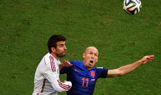 Spain's defender Gerard Pique (L) vies with Netherlands' forward Arjen Robben (R) during a Group B football match between Spain and the Netherlands at the Fonte Nova Arena in Salvador during the 2014 FIFA World Cup on June 13, 2014. Photo:  AFP/Getty Images