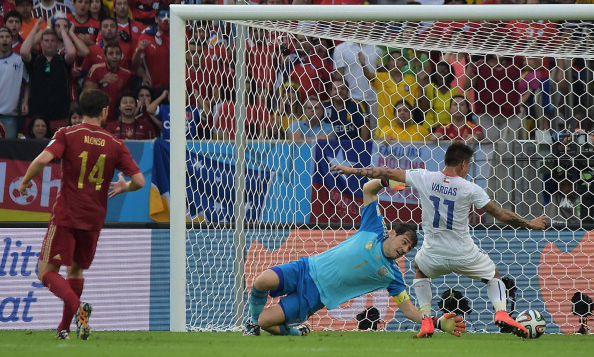Chile's forward Eduardo Vargas (R) strikes to score Chile's first goal as Spain's goalkeeper and captain Iker Casillas (C) defends and Spain's midfielder Xabi Alonso watches on during a Group B football match between Spain and Chile in the Maracana Stadium in Rio de Janeiro during the 2014 FIFA World Cup on June 19, 2014. Photo: AFP/Getty Images