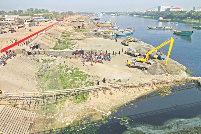 The BIWTA yesterday sent two diggers to Kanchpur bridge on the Shitalakkhya to evict sand traders who occupied the river way beyond the walkway, marked in red, built on the bank. Photo: Amran Hossain