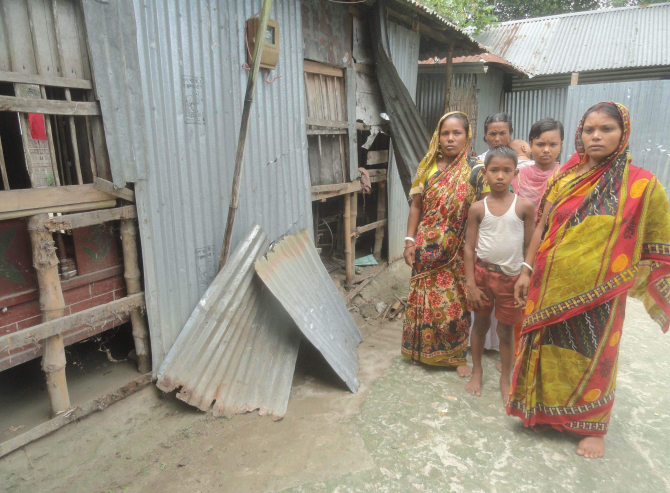 Members of a panic-stricken Hindu family stand in front of their house vandalised by a gang of extortionists at Nizpara village in Lalmonirhat Sadar upazila on Monday. Photo: Star
