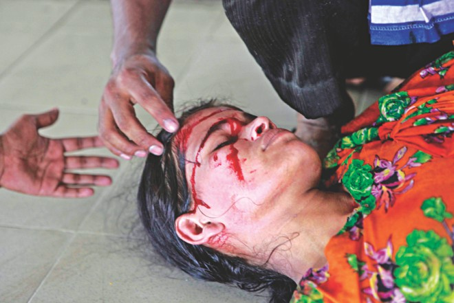 A wounded female worker lying on the road. Photos: Courtesy