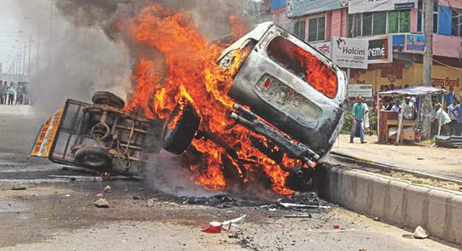 This Star photo taken on May 20 shows the car of Phulgazi upazila chairman Ekramul Haq burning after an arson attack in Feni. The easy bike used by the attackers is also in flames.