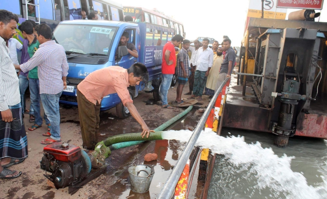 To keep a ferry operational, a worker pumps out water that had entered through the cracks of the vessel at Lebukhali terminal on the Paira River on  Barisal-Patuakhali road.   PHOTO: STAR
