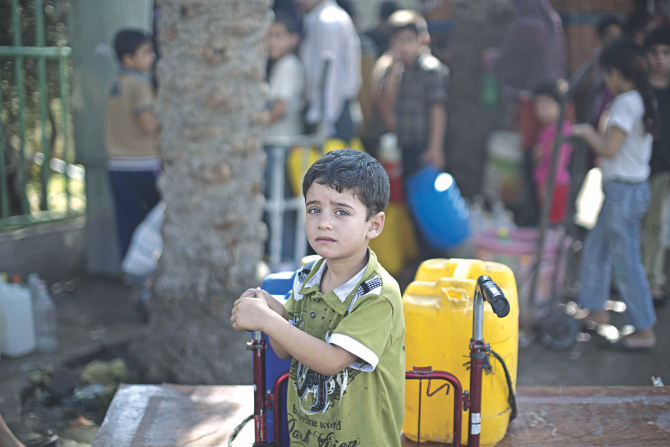 A Palestinian child waits to fill plastic bottles and water containers with drinking water from a public tap in Jabalia in the northern Gaza Strip yesterday during a short-lived truce agreed between the warring parties. Israeli military yesterday resumed its assault on Gaza after Hamas shunned an extended lull accepted by Israel, medics said. Photo: AFP