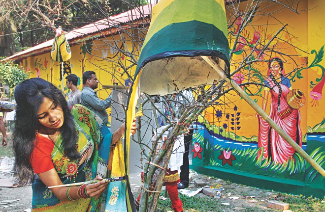 A student puts finishing touches to an artwork at the Faculty of Fine Arts of Dhaka University yesterday afternoon. The item, among others, will be used in the Pahela Baishakh procession in the capital today. Photo: Star