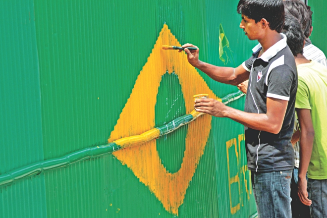 A football fan painting the flag of Brazil on a corrugated iron sheet fence at the capital's Ahmedbagh in Sabujbagh as the nation prepares for the World Cup. Photo: Sk Enamul Haq