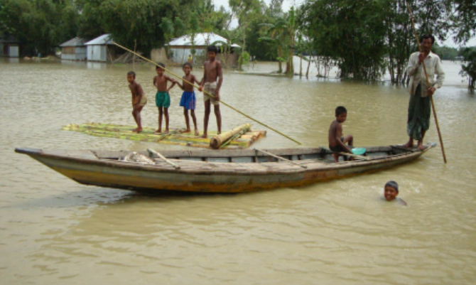 A man and some kids row a boat and a raft in flood-hit Sindurna village under Hatibandha of Lalmonirhat. Photo: Star