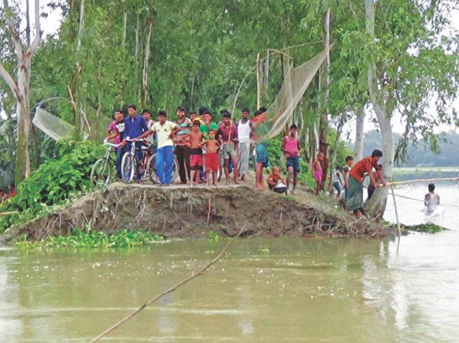 People stand on what is left of the dyke in Boirati village under Kaliganj upazila in the district. Boirati and two other villages got flooded as part of the dyke was washed away by the Teesta river yesterday afternoon. Photo: Star
