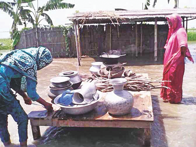 Two women cook in their front yard in ankle-deep water as the flooding and erosion by the Jamuna continue to devastate the Phulchhari upazila of Gaibandha. The photo was taken yesterday at Paglar Char. Photo: Star