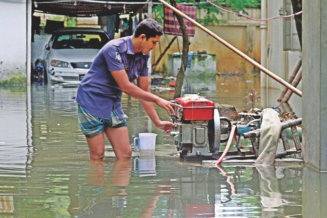 A policeman pumps out water from the residence of Dhaka SP on Shaheed Capt Monsur Ali Road in the capital's Ramna area yesterday. The SP has been staying out of the house -- at office or relative's. Downpours over the last few days and a sewerage line damage due to Moghbazar-Mouchak flyover construction led to the waterlogging in and around the neighbourhood. The photo was taken around 3:00pm yesterday.  Photo: Anisur Rahman