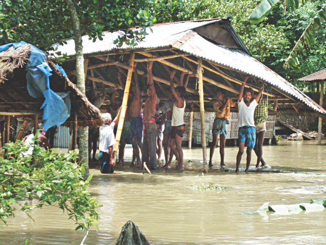 People dismantle their home in Dewabari of Hatibandha in Lalmonirhat yesterday to take it to a safer place as the over-flowing Teesta floods a large portion of the north.  Photo: Dilip Roy