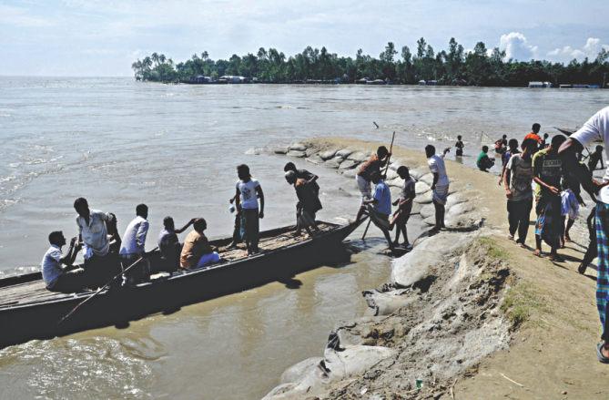 Jamuna washed away 300 metres of a dyke early yesterday flooding homes of thousands and their cropland. Photo: Star